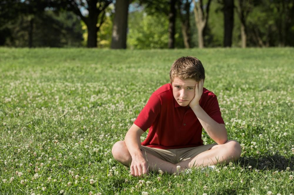 A stressed-looking boy sitting in the garden